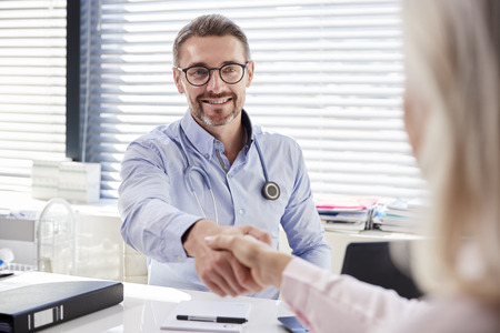 Female Patient Shaking Hands With Doctor Sitting At Desk In Office