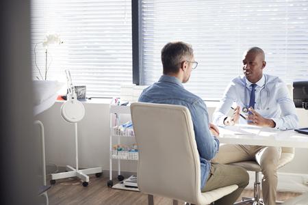 Reifer männlicher Patient in Absprache mit Arzt im Büro