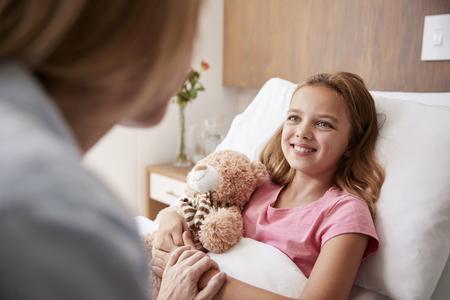 Madre visitando a su hija acostada en la cama en la sala del hospital