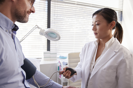 Male Patient Having Blood Pressure Taken By Female Doctor In Office