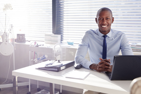 Portrait Of Smiling Male Doctor Sitting Behind Desk In Office