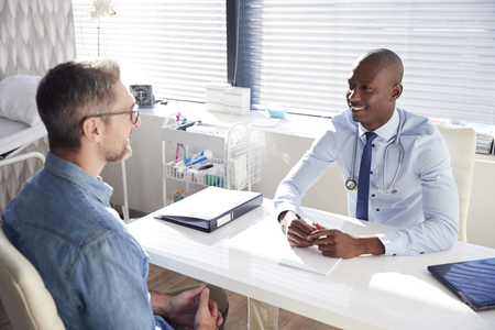 Mature Male Patient In Consultation With Doctor In Office Stock Photo