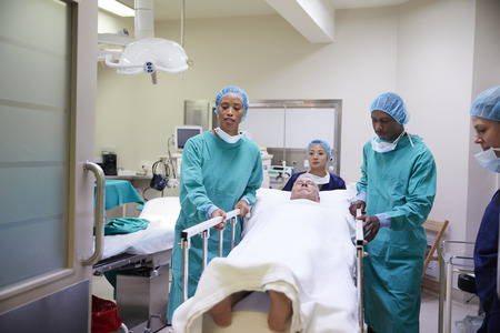 Surgical Team Wheeling Senior Male Patient Out Of Hospital Operating Theatre 写真素材