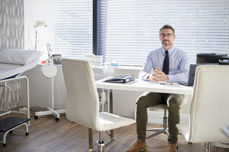 Portrait Of Mature Male Doctor Sitting Behind Desk In Office