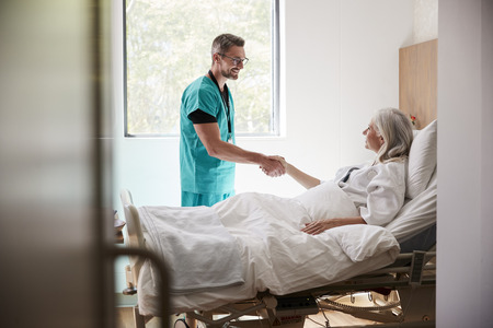 Surgeon Visiting And Shaking Hands With Mature Female Patient In Hospital Bed Zdjęcie Seryjne