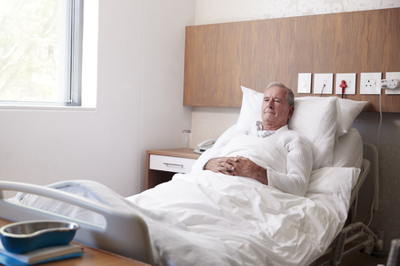 Senior Male Patient In Hospital Bed In Geriatric Unit