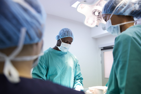 Surgical Team Working On Patient In Hospital Operating Theatre 写真素材
