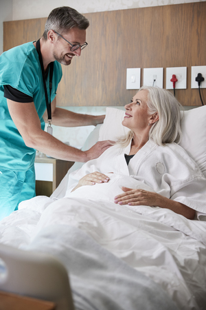 Surgeon Visiting And Talking With Mature Female Patient In Hospital Bed
