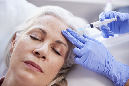Beautician Giving Mature Female Patient Botox Injection In Forehead Archivio Fotografico