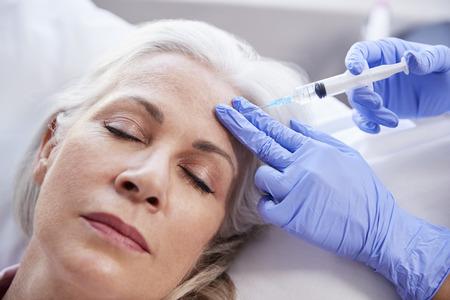 Kosmetyczka daje dojrzałej pacjentce zastrzyk botoksu w czoło Zdjęcie Seryjne