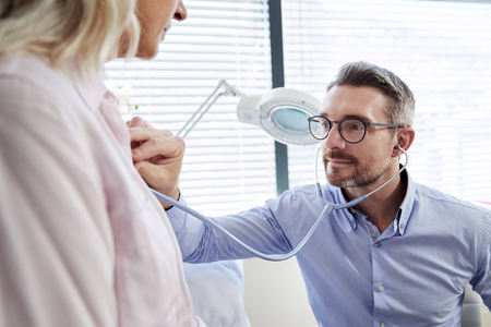 Mature Female Patient Having Medical Exam With Doctor In Office