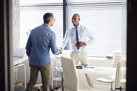 Mature Male Patient Shaking Hands With Doctor In Office Standard-Bild