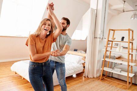 Couple s'amusant dans une nouvelle maison dansant ensemble