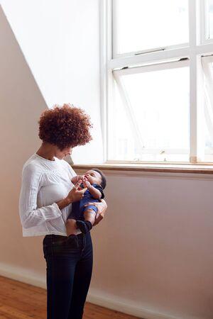 Madre cariñosa sosteniendo bebé recién nacido durmiendo por ventana en casa en apartamento tipo loft Foto de archivo