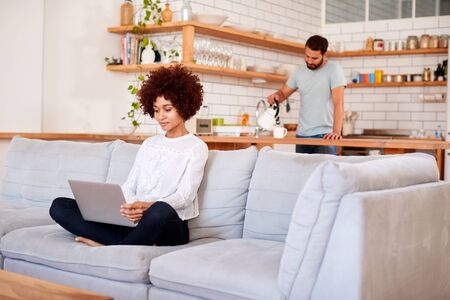 Woman Relaxing Sitting On Sofa At Home Using Laptop Computer With Man In Kitchen Pouring Drink Banque d'images - 124541802