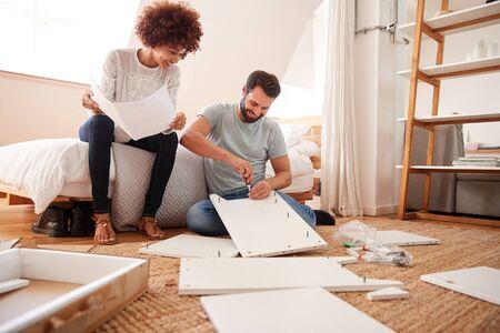Paar in nieuw huis dat zelfmontagemeubels in elkaar zet Stockfoto