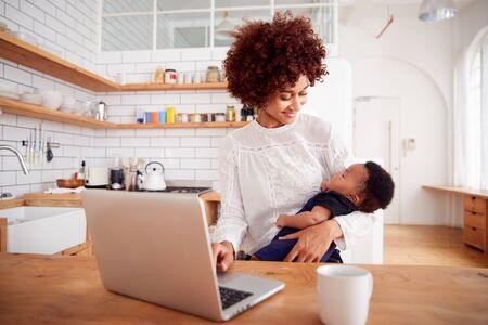 Mère multi-tâches tient un bébé endormi et travaille sur un ordinateur portable dans la cuisine
