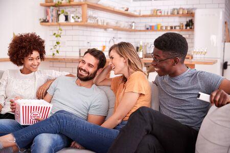 Gruppe von Freunden, die auf dem Sofa sitzen und sich zu Hause einen Film ansehen, während sie Popcorn essen Standard-Bild