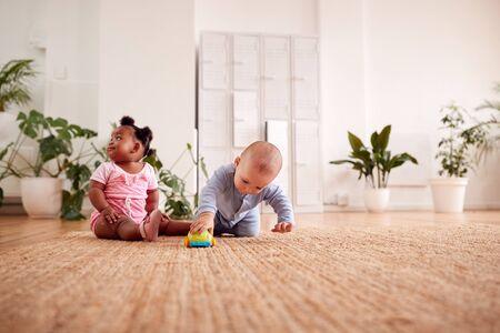 Niño y niña jugando con juguetes sobre una alfombra en casa juntos