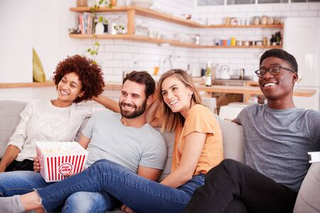 Group Of Friends Sitting On Sofa And Watching Movie At Home Whilst Eating Popcorn Banque d'images - 124542149