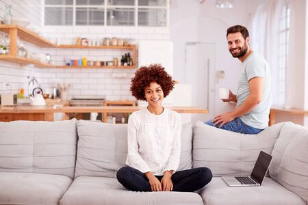 Portrait Of Couple Relaxing On Sofa At Home Looking At Laptop Together Banque d'images - 124542270