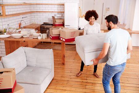 Coppia sorridente che trasporta mobili nella nuova casa il giorno del trasloco Archivio Fotografico