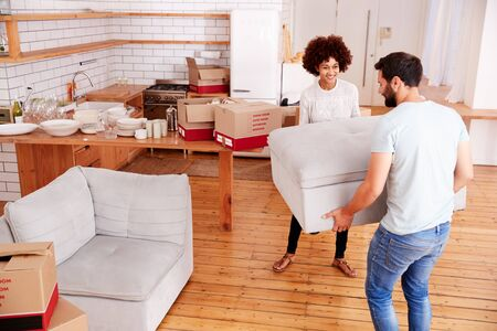 Smiling Couple Carrying Furniture Into New Home On Moving Day
