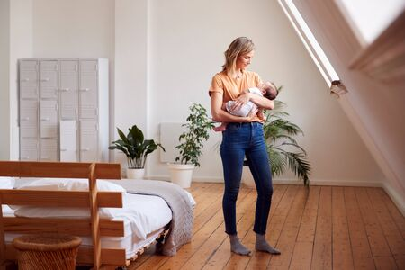 Loving Mother Holding Newborn Baby At Home In Loft Apartment