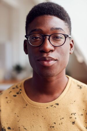 Portrait Of Young Man Wearing Glasses In Loft Apartment