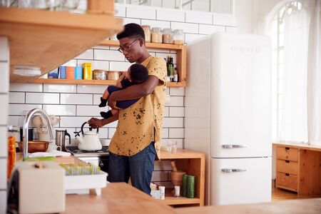 Multi-Tasking Father Holds Baby Son And Pours Kettle In Kitchen