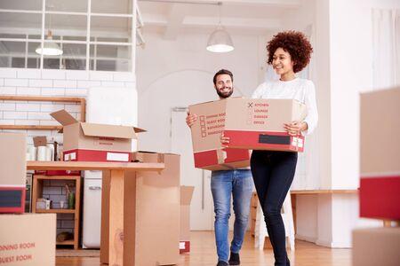 Lächelndes Paar, das am Umzugstag Kisten in ein neues Zuhause trägt Standard-Bild
