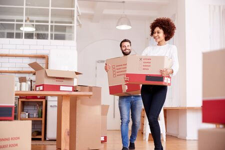 Smiling Couple Carrying Boxes Into New Home On Moving Day Stock Photo