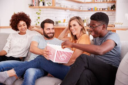 Group Of Friends Sitting On Sofa And Watching Movie At Home Whilst Eating Popcorn Banco de Imagens