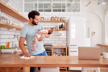 Multi-Tasking Father Holds Sleeping Baby Son And Cleans In Kitchen Banco de Imagens