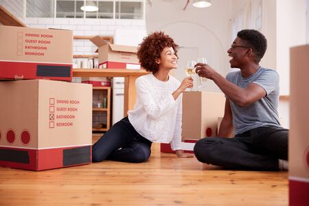 Pareja celebrando mudarse a casa nueva bebiendo champán