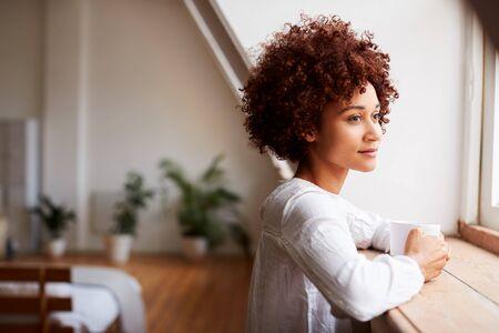 Jonge vrouw ontspannen in loft appartement kijkt uit raam met warme drank