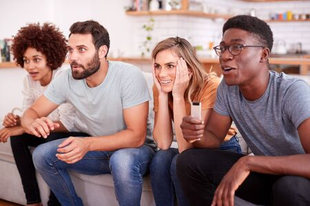 Excited Group Of Friends Sitting On Sofa And Watching Sports On TV Banque d'images - 124542567