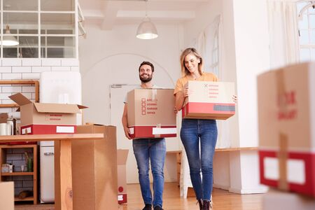 Smiling Couple Carrying Boxes Into New Home On Moving Day Banco de Imagens