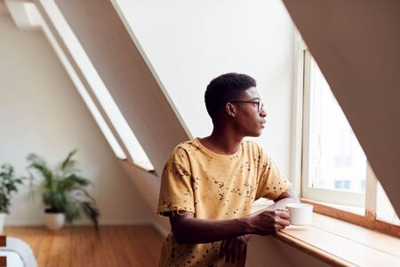 Young Man Relaxing In Loft Apartment Looking Out Of Window With Hot Drink