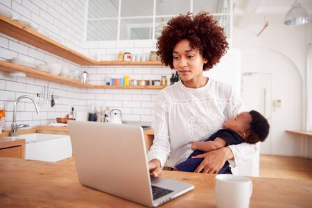 Multi-Tasking Mother Holds Sleeping Baby Son And Works On Laptop Computer In Kitchen Banco de Imagens