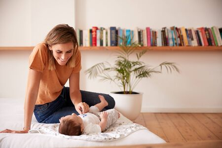 Loving Mother With Newborn Baby Lying On Bed At Home In Loft Apartment