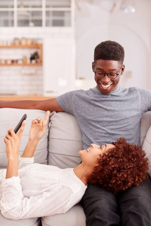 Young Couple Relaxing On Sofa At Home Looking At Mobile Phone Together Banco de Imagens