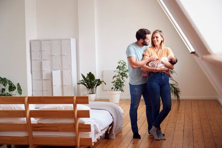 Loving Parents Holding Newborn Baby At Home In Loft Apartment Stock Photo - 124542935