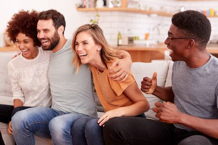 Excited Group Of Friends Sitting On Sofa And Watching Sports On TV