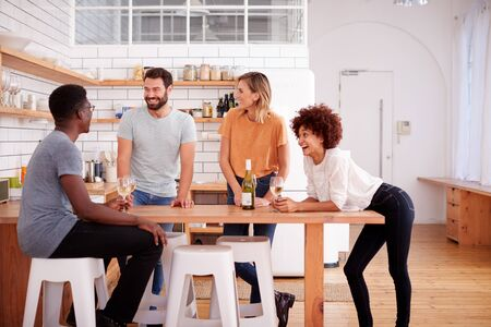 Two Couples Relaxing In Kitchen At Home With Glass Of Wine Talking Together