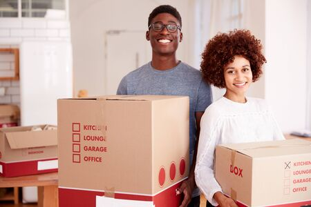 Portrait Of Smiling Couple Carrying Boxes Into New Home On Moving Day