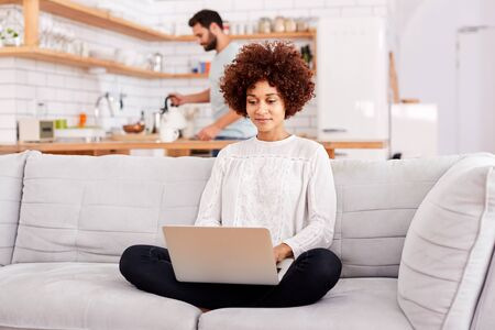 Woman Relaxing Sitting On Sofa At Home Using Laptop Computer With Man In Kitchen Pouring Drink