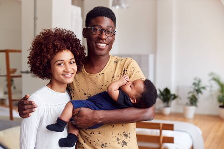 Portrait Of Loving Parents Holding Newborn Baby At Home In Loft Apartment Banco de Imagens