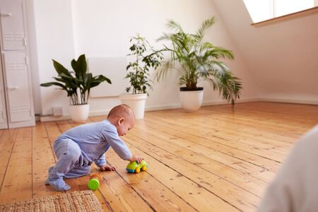 Baby Boy Playing With Toys On Floor At Home Banco de Imagens