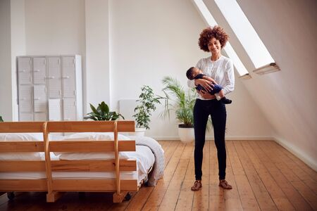 Portrait Of Loving Mother Holding Newborn Baby At Home In Loft Apartment